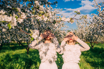 two twin sisters in a cherry orchard