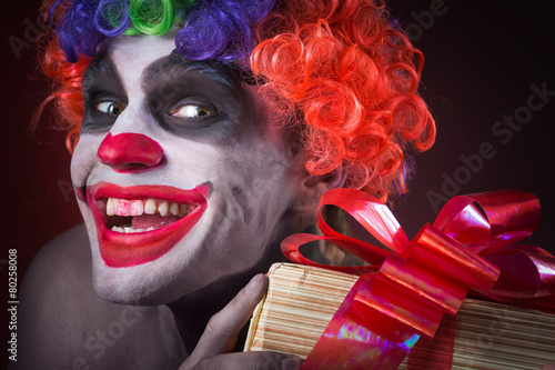 Fotobehang Begraafplaats scary clown makeup and with a terrible gift