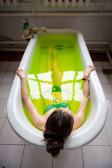 Woman in a bathtub with green water
