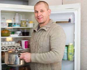 Smiling man with pan near fridge