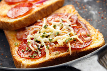 Hot sandwiches with pepperoni frying pan closeup