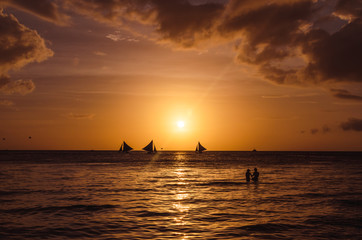 Sailing boats and silhouette of couple over a beautiful sunset