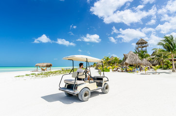 Young man driving golf cart along tropical sandy beach