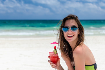 Young cute woman with fresh cocktail at tropical sandy beach