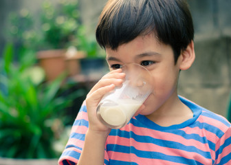 Littl boy drinking milk in the park vintage colo style