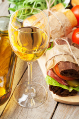 White wine glass, sandwiches and salad