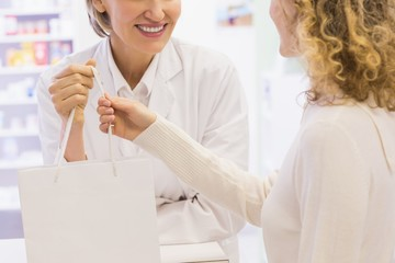 Pharmacist and costumer holding paper bag