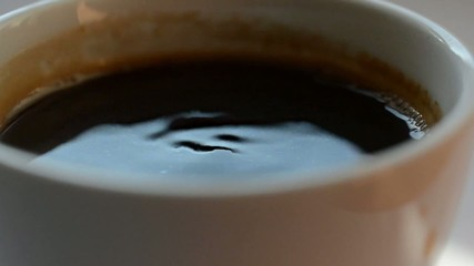Drop of coffee to white cup of coffee slow motion