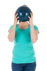 Woman is holding a bowling ball just before her head