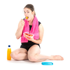Stting woman with purple towel eating fresh fruits