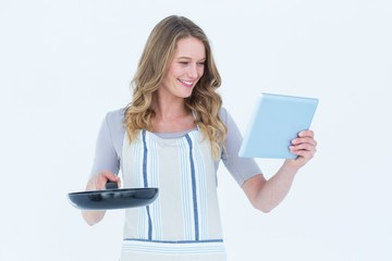 Smiling woman holding frying pan and tablet pc