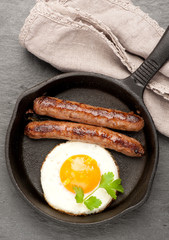 grilled sausages in a frying pan and fried eggs.  top view