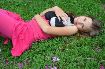 Девочка лежащая на газоне с маленьким щенком