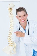 Smiling doctor pointing an anatomical spine