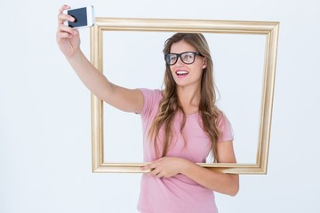 Pretty blonde taking a selfie of herself holding frame
