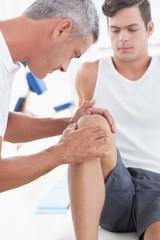 Doctor examining his patient knee