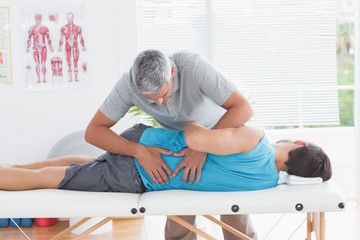 Doctor examining man back