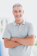 Smiling doctor standing arms crossed and looking at camera