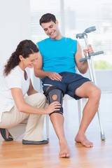 Doctor examining her patient knee
