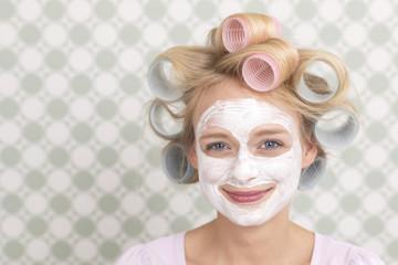Junge Frau mir großen Lockenwicklern und Gesichtsmaske