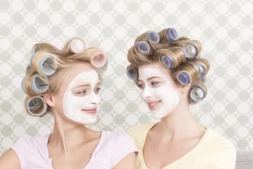 Junge Frauen mit großen Lockenwicklern und Gesichtsmaske