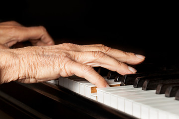 Old person's hands playing piano. Active senior close up