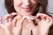 Leinwandbild Motiv Junge Frau biegt Zigarette durch