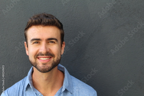 Portrait of a happy young man smiling on gray background - 80269613