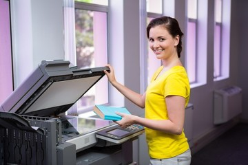 Student photocopying her book in the library