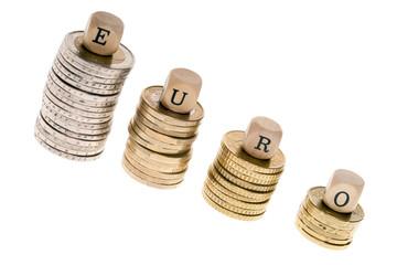Geldstapel und Holzwürfel mit dem Wort Euro isoliert
