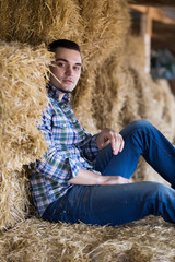 farm worker sitting on haystack