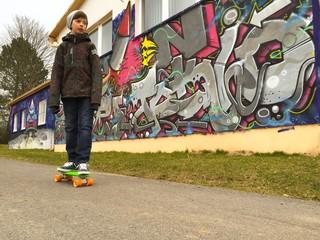 Junge fährt Longboard an Graffiti Wand