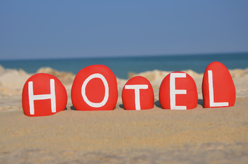 Hotel, name composed with red stone letters on the sand
