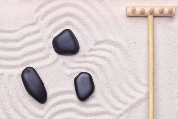Zen garden with some black zen rocks and wave pattern in the san