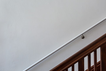 Wooden staircase in front of white wall with handrail