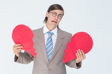 Geeky businessman crying and holding broken heart card