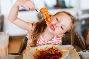 Little girl eating spaghetti