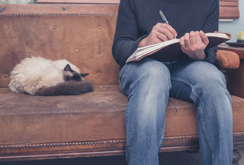 Man sitting on sofa writing in notebook