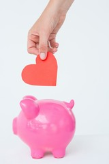 Woman holding piggy bank and red heart
