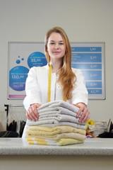 Mitarbeiterin einer Textilreinigung am Tresen mit Handtüchern