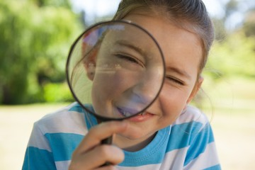 Cute little girl looking through magnifying glass