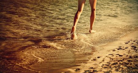 Woman is running ahead on beach of sea