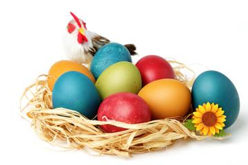 Nido di paglia pieno di uova colorate per la Pasqua