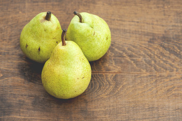 Pears on rustic wooden table; focus on front pear (Shallow DOF)