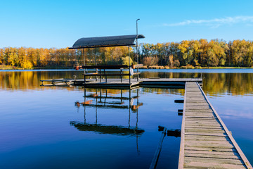 beautiful fall reflections in a lake with a fishing dock
