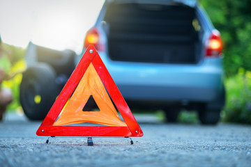 Changing  tire on broken car on road with red warning triangle