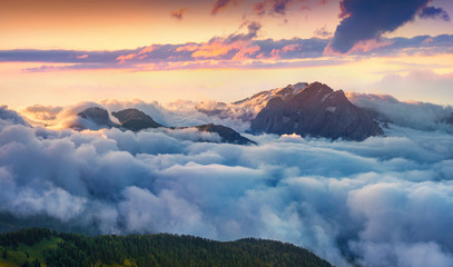 Panorama of the sunrise in foggy Val di Fassa valley