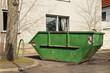 Leinwandbild Motiv Ein grüner Container für Abfall steht vor einem Wohnhaus