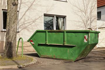 Ein grüner Container für Abfall steht vor einem Wohnhaus