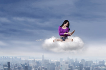 Female teenage with tablet on the cloud